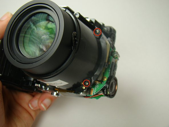 Remove the four black screws at the corners of the lens housing.