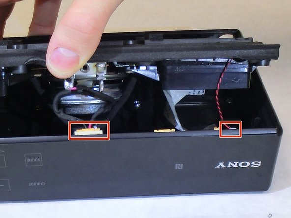 Locate the two wire connections as shown underneath of the speaker assembly and unplug them using a pair of tweezers.