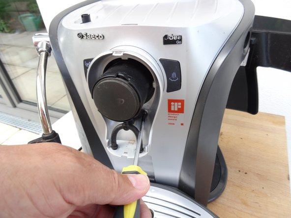 Drehe die beiden Torx T10 Schrauben am Kaffeeauslauf heraus.