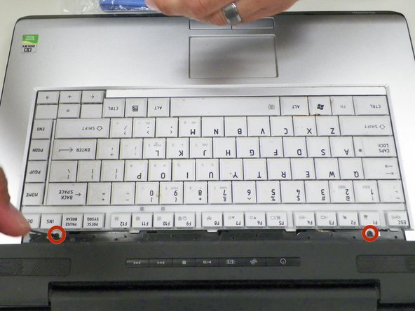 Remove 2 Phillips 3.1 mm size screws from each side above the keyboard.