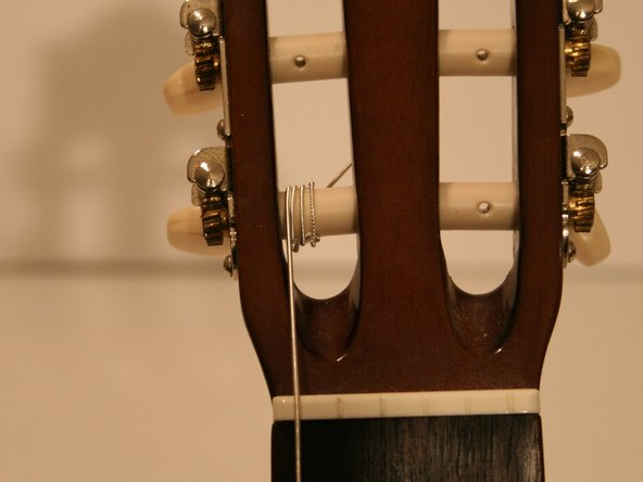 "As the string winds around the tuning peg, make sure that the string passes over the loose end from the knot at least once. This will prevent ""slipping"" (detuning) during tuning and will help keep the knot tight."