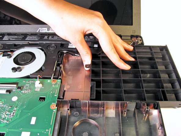 Remove the spacer from the laptop by gently sliding it towards the right edge of the laptop.
