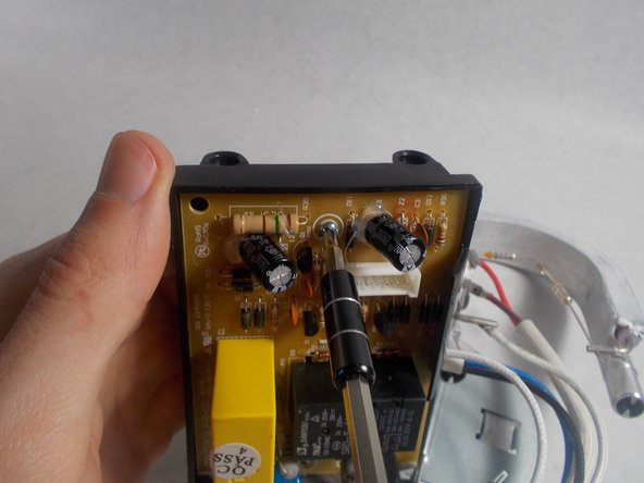 In order to remove the small housing that covers the motherboard, remove the lone screw with a PH1 bit.