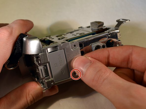 On the bottom of the device, remove the last 3mm Philips screw on the last panel./Make a close up of the screw for this picture.