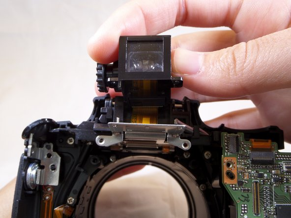 Carefully, as the wire ribbon is slowly removed out of its slot when viewfinder is pulled out.
