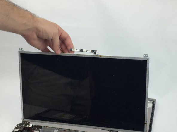 Carefully lift up the screen for an easier removal of the webcam. Then gently remove the connector by sliding it out of the webcam.