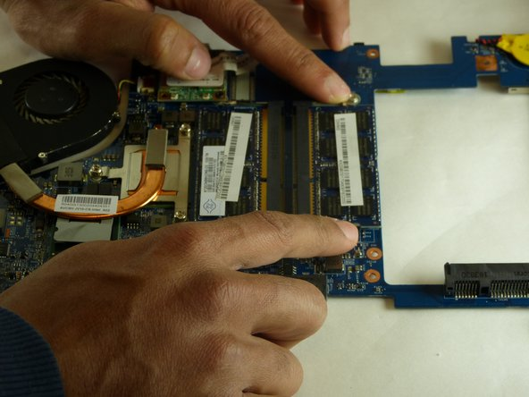 To replace the RAM, hold the both metal prongs that are on the sides of the RAM to the side.