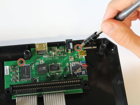 Remove the smaller screws located on the green motherboard with the Phillips #000 screwdriver.