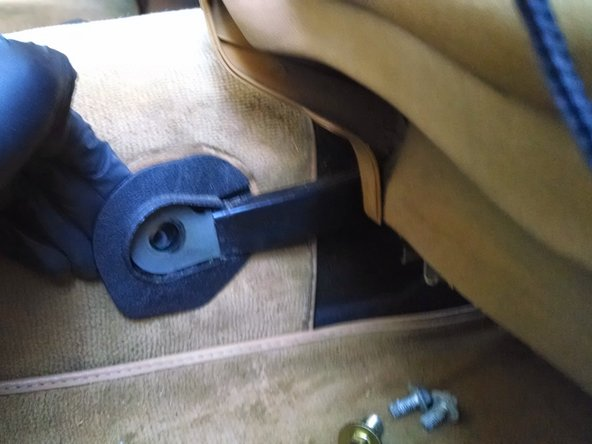 Image 1/3: Behind the end of the seat rail you will find a large concave washer and a smaller rubber sealing washer (the hole that the bolt goes through is exposed to the outside). Make sure to note their orientation for replacement.