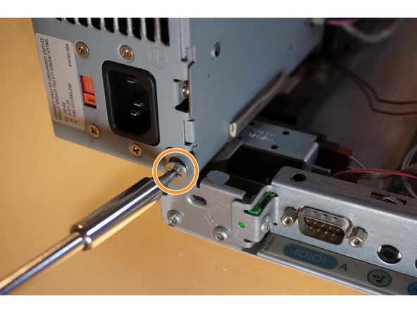 A single T5 Torx screw holds the power supply to the chassis.