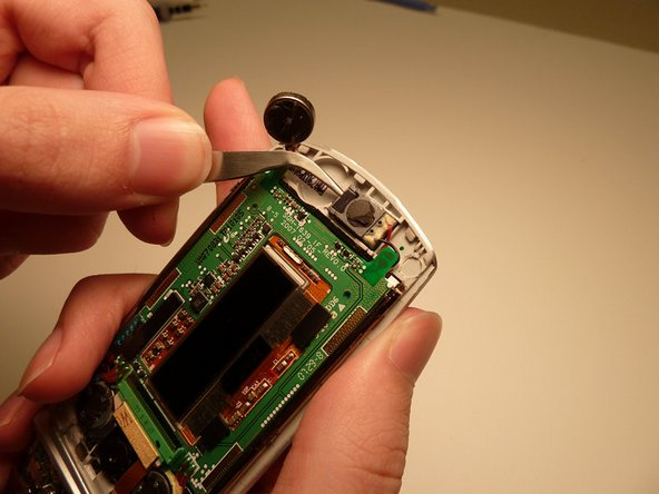 Gently grasp and lift the speaker from the cell phone using tweezers.