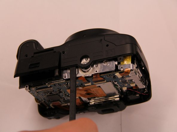 Using the spudger and plastic opening tool, pry the bottom of the front panel of the camera over the tripod mount.
