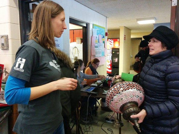 At a Hennepin County Fix-It Clinic, a visitor named Greta talks to a volunteer about repairing a lamp.