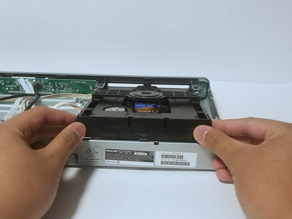 Lift the tray out of the DVD player from the  back.