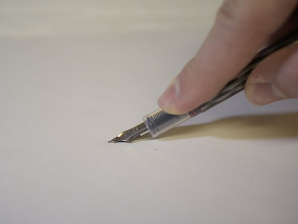 Press the nib of the pen down onto the flat surface.