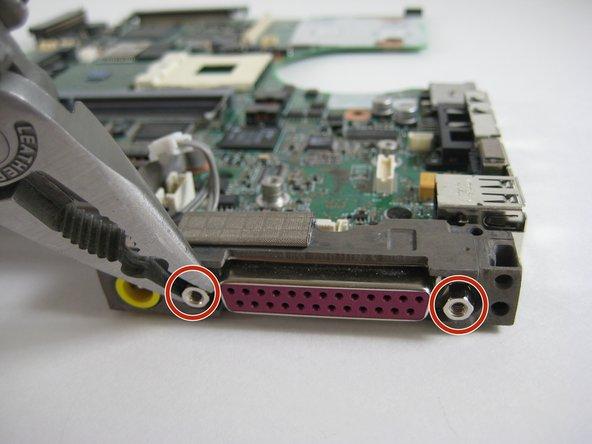 À l 'aide d' un tournevis ou d 'une paire de pinces à bec mince, retirez les deux vis de fixation situées à côté du port parallèle rose à l'arrière de la carte mère.