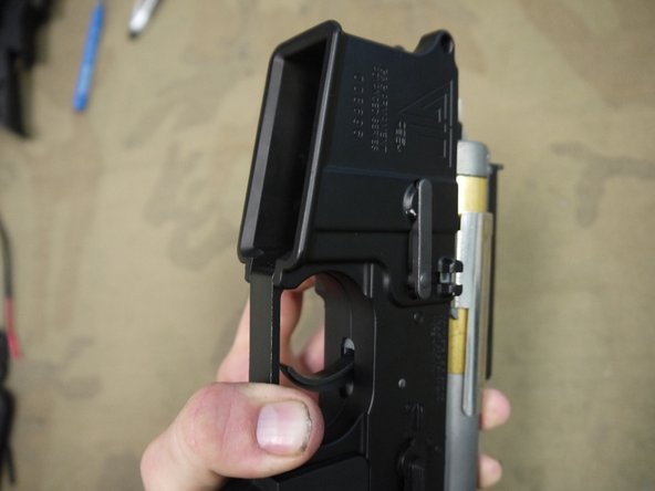 Start by pushing the magazine release button into the receiver, so that the catch section on the other side of the gun is protruding as far outward as possible.