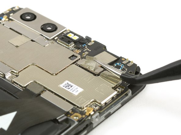 Use tweezers to carefully loosen the bottom end of the adhesive strip, that holds down the flex connector of the front facing camera.
