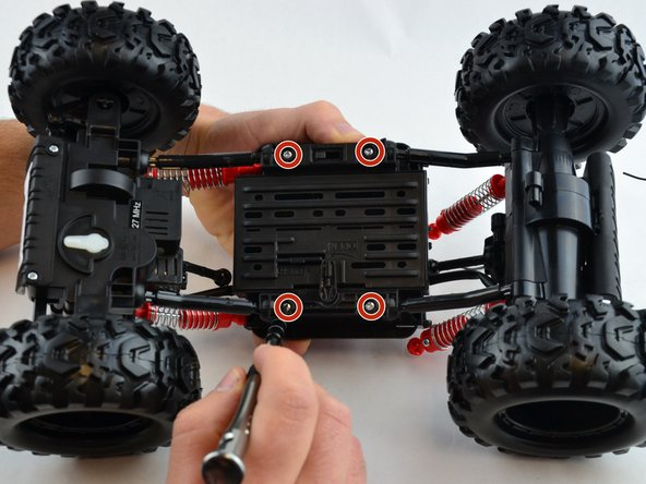 Flip the R/C truck over and remove the four 10 mm bottom under-body plate screws using the driver and bit PH2.