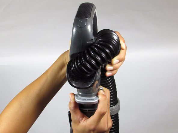 Locate the black hose on the back of the vacuum.