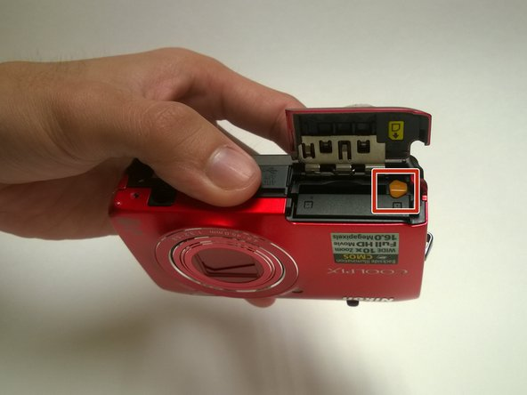 Rotate the orange battery clip in the camera to release the battery.