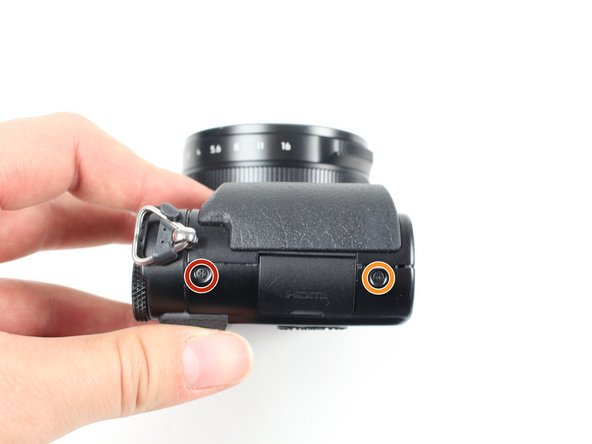 Use a Phillips #000 screwdriver to remove the two 3.5 mm screws, one below the lens and one on the left side.