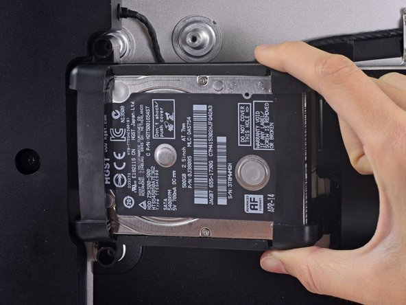 The hard drive is attached by a single SATA power/data cable—do not attempt to fully remove it from the iMac yet.