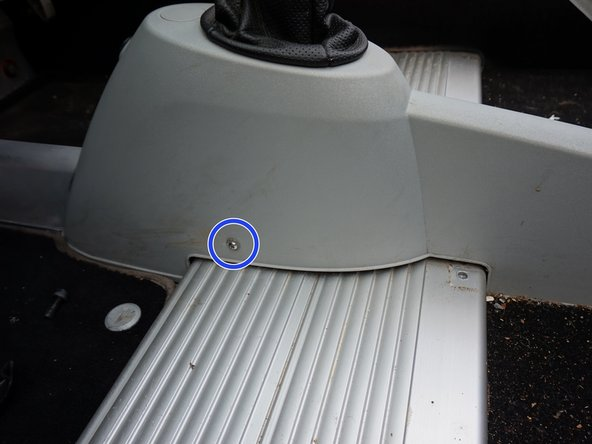 Image 1/2: With the shifter gaiter/boot still attached, lift the plastic trim high enough to reach the underside. This will give you access to remove the clips holing the gaiter/boot the the plastic shifter trim.