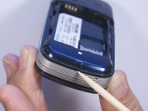 Image 1/2: Use spudger to separate phone casing and inside as shown.