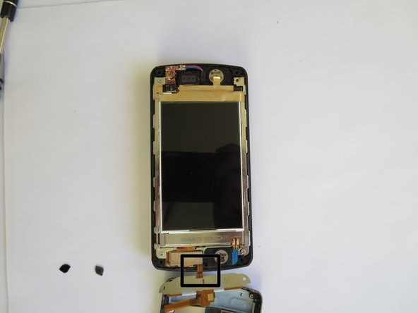 Image 2/2: The frame should still be connected to the rest of the phone by the orange tab.