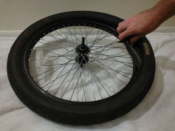 Beginning with the nozzle, remove the damaged inner tube by pulling it out from in between the tire and the rim. Continue to pull out the rest of the tube.