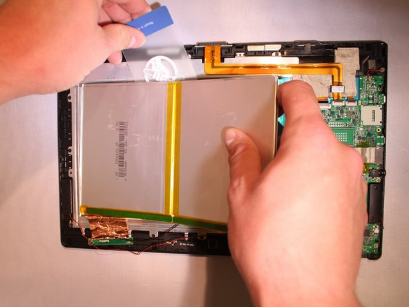 Image 2/3: The battery is glued onto the device. To remove it, use a nylon spudger or plastic card to slide underneath the battery and scrape back and forth to remove the glue until the battery is removed from the device.