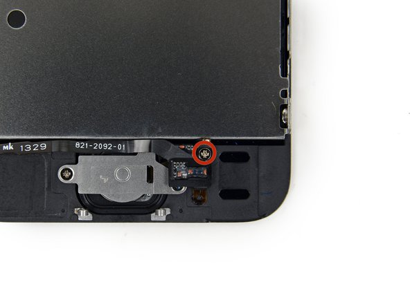 Image 1/2: The captive screw is fastened to the home button cable by a spring contact backing. During reassembly, ensure the contact is in the correct orientation—on the side of the screw nearest the LCD.