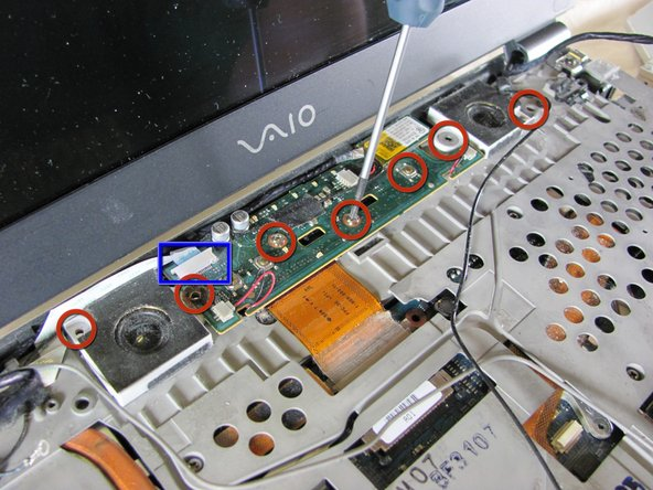Image 1/1: Before removing the assembly, disconnect the ribbon cable located at the top left corner of the assembly.