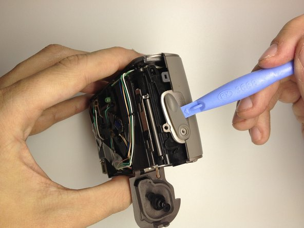 Image 2/2: Using a plastic opening tool, gently pry the switch upwards to remove it.