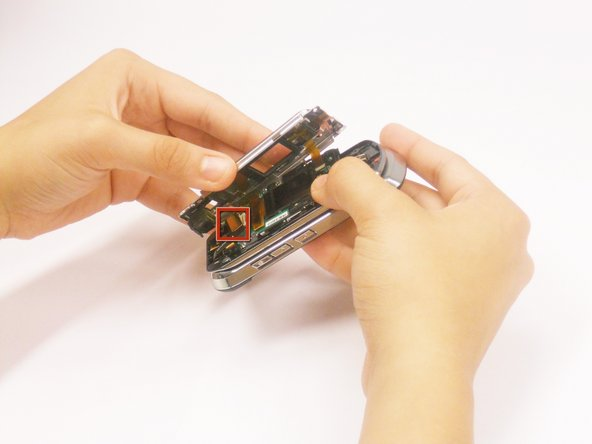 Use the flat end of the plastic opening tool to unclip the cable ribbon from the logic board