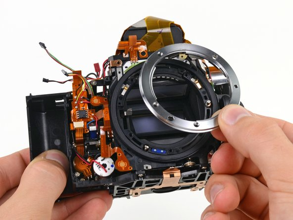 "This is the point in the teardown when stuff just starts coming out of the device left and right. A lens mount here, a ribbon cable there, whatever that is over there... the only thing that could make this better is if it was made into an awesome montage and set to ""You're the Best,"" à la Karate Kid."