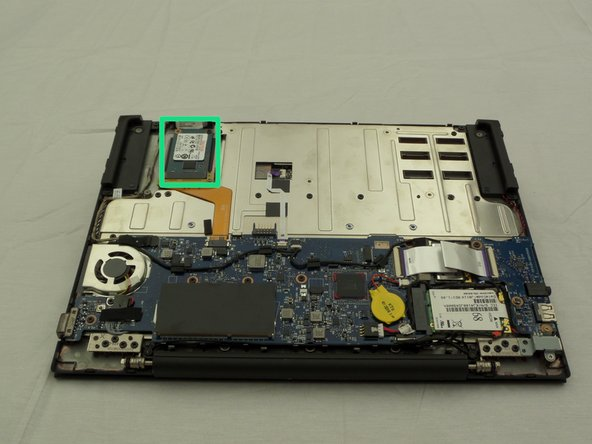 Find the SSD located on a corner of the side directly opposite where the laptop screen and device body are connected.
