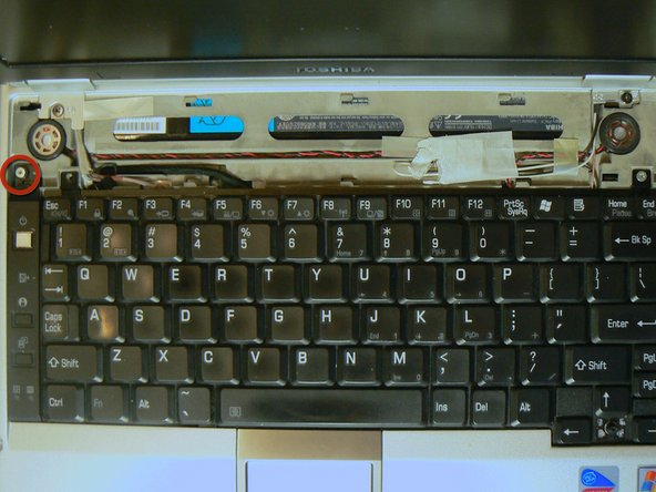 Remove the Torx screw holding the left keyboard tab in place, and lift it to release.
