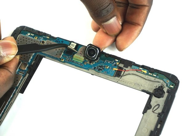 To remove the bigger, back-facing camera, use the precision tweezers to slide the silver ribbon cable out of the ZIF connector.
