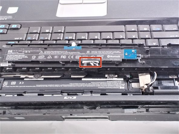 Place the plastic piece on the keyboard so the ribbon strip is easily accessible.