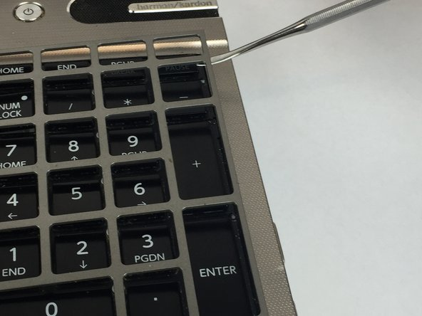 Use a plastic opening tool to pry up the keyboard cover.