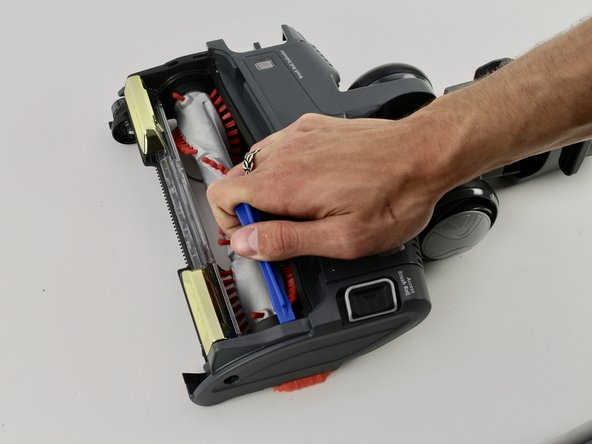 Use the iFixit Opening Tool to pry the side of the vacuum open.