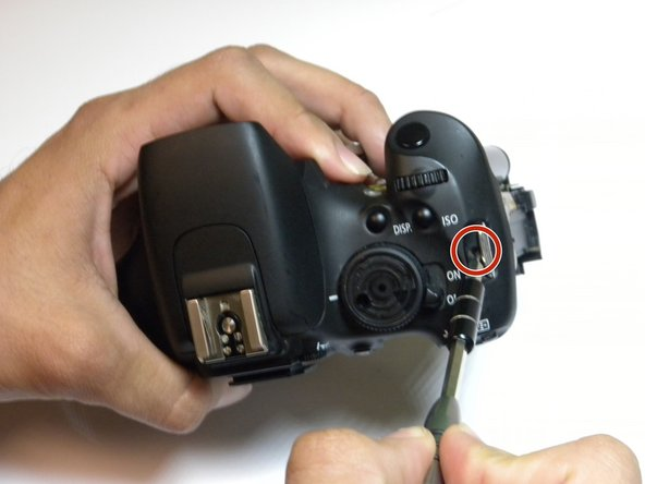 On the opposite end of the camera, unscrew the screw next to the power switch using the same tool.