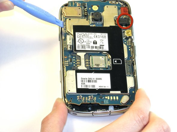 Image 1/1: Remove the motherboard assembly from left to right, using caution near the audio jack on the right side of the device.