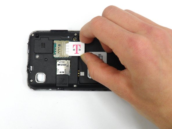Remove SIM card by pushing down and away from the slot, then pulling it out toward the bottom edge of the phone.