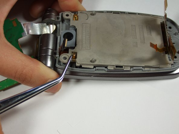 Use a tweezers to lift up the main LCD