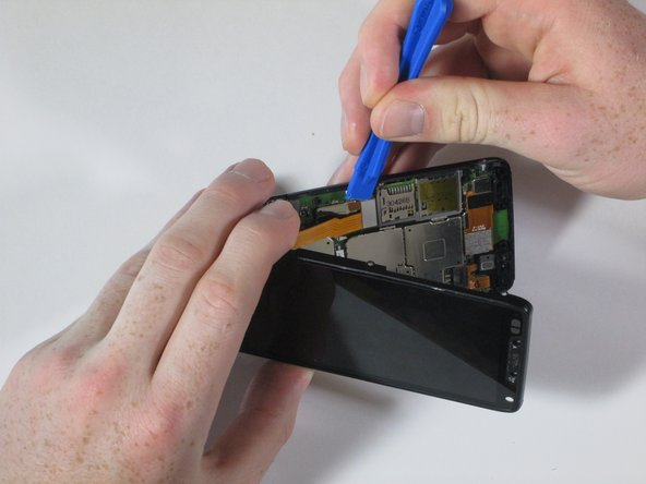 Image 3/3: Once the snap connection is undone, pull apart the front assembly from the rest of the phone.