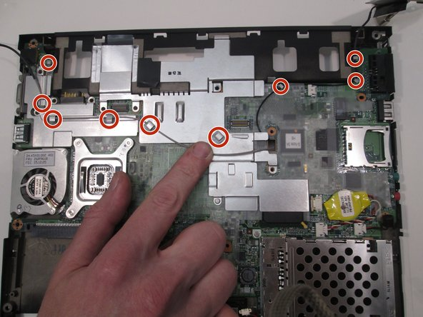 Remove the metal plate covering the motherboard by removing the gray wire from the indicated hooks and pulling the plate up. While you are here remove the other black wire from the indicated hooks as well.