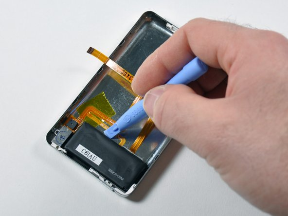 Image 1/3: Insert an iPod opening tool in between the metal case and battery at the location illustrated by the picture.